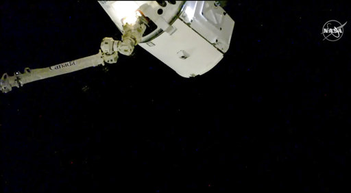 In this image taken from NASA Television, the SpaceX Dragon cargo spacecraft is captured by a robotic arm for docking to the International Space Station, Saturday, Dec. 8, 2018. A SpaceX delivery full of Christmas goodies has arrived at the International Space Station. The Dragon capsule pulled up at the orbiting lab Saturday, three days after launching from Florida. [Photo: AP/ NASA TV]