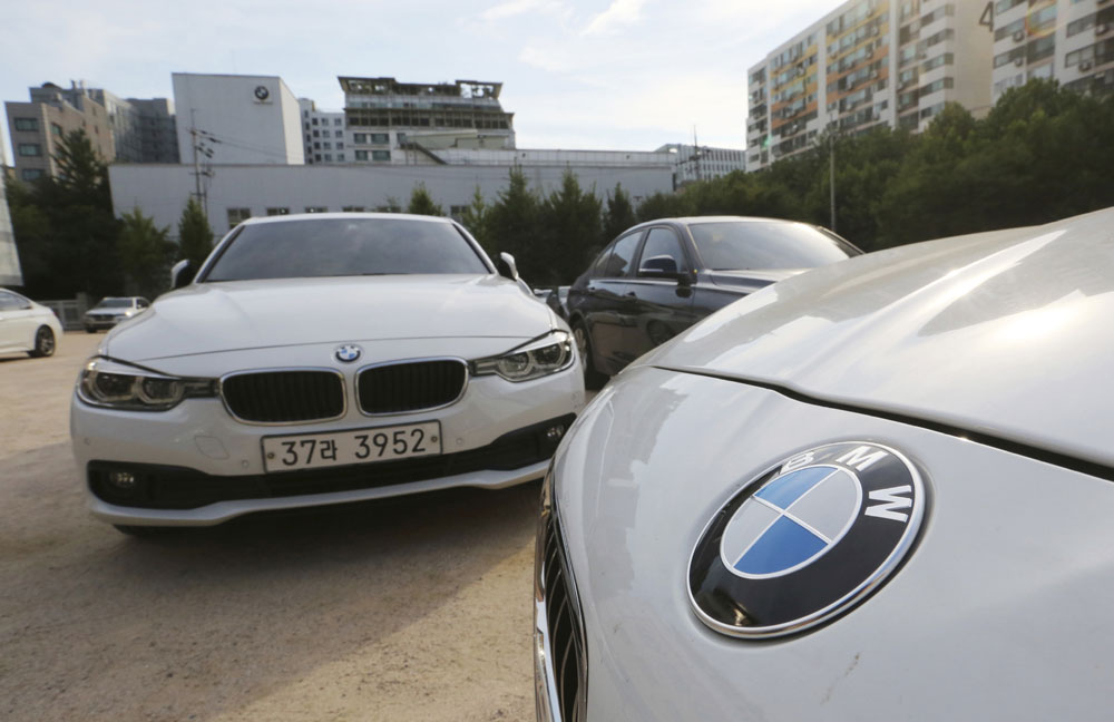 In this Aug. 14, 2018 file photo, BMW cars are parked for an emergency safety check at the playground of an elementary school near a BMW service center in Seoul, South Korea. South Korea says on Monday, Dec. 24, 2018. it will fine BMW 11.2 billion won ($9.9 million) and file a criminal complaint against the company with state prosecutors over an allegedly botched response to dozens of engine fires reported in the country. [Photo:AP]