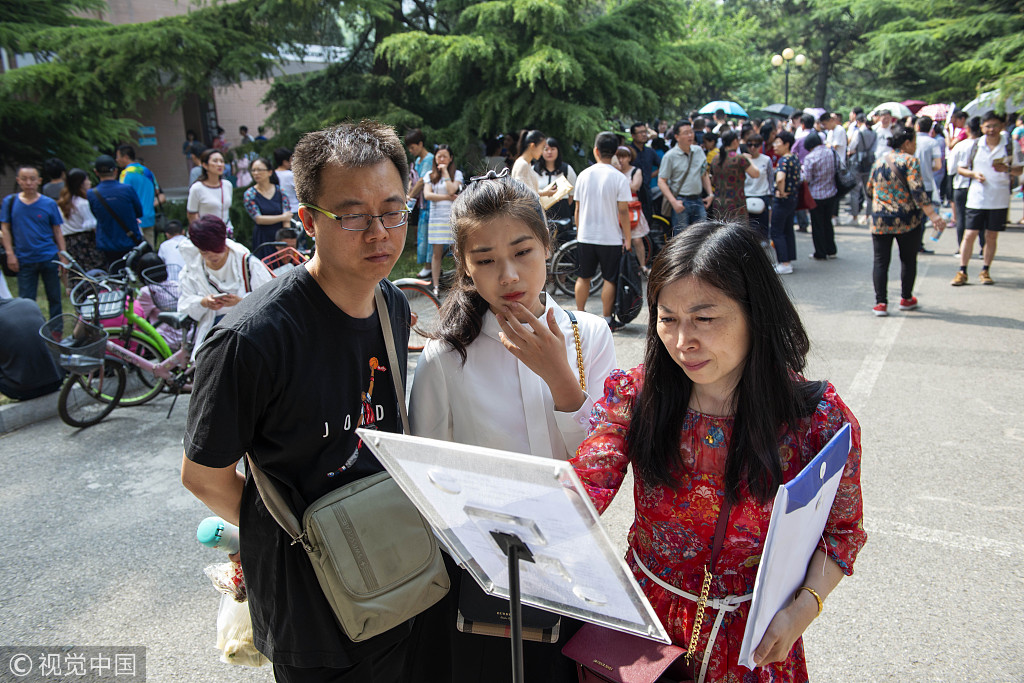 A student, along with her parents, reads test rules as she takes part in an independent enrollment examination of Communication University of China in Beijing, on June 12, 2018. [Photo: VCG]