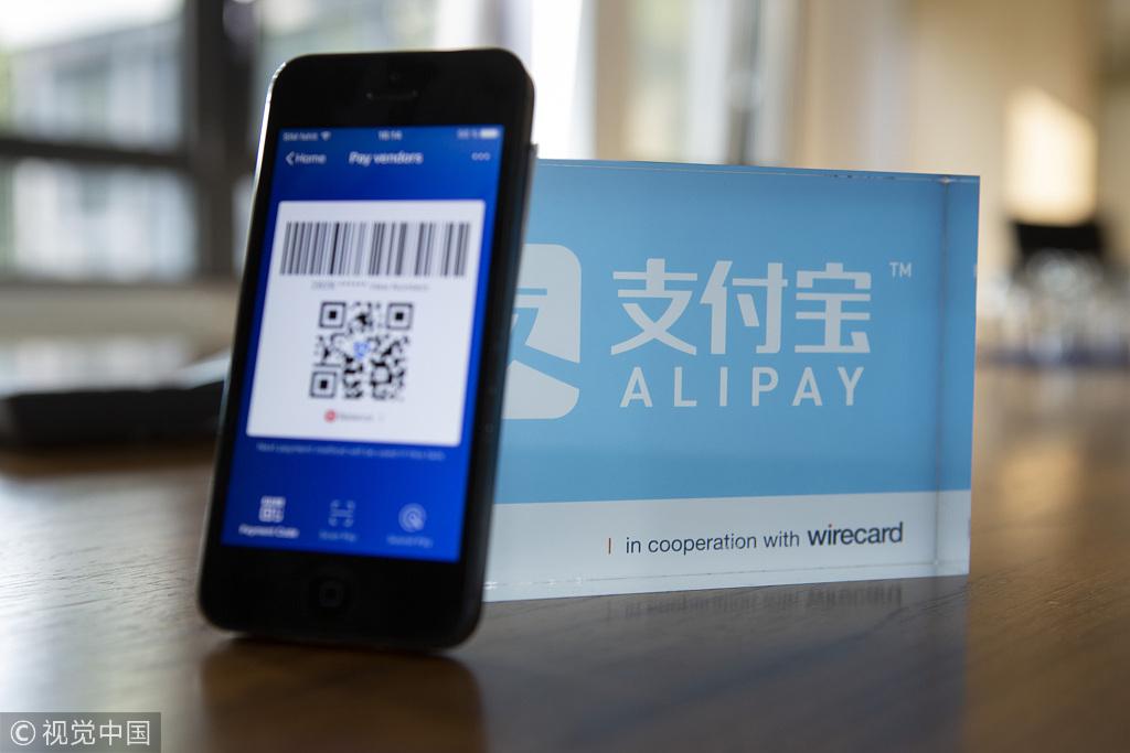 An Alipay digital payment app logo and smartphone sit on a desktop. [Photo: VCG]