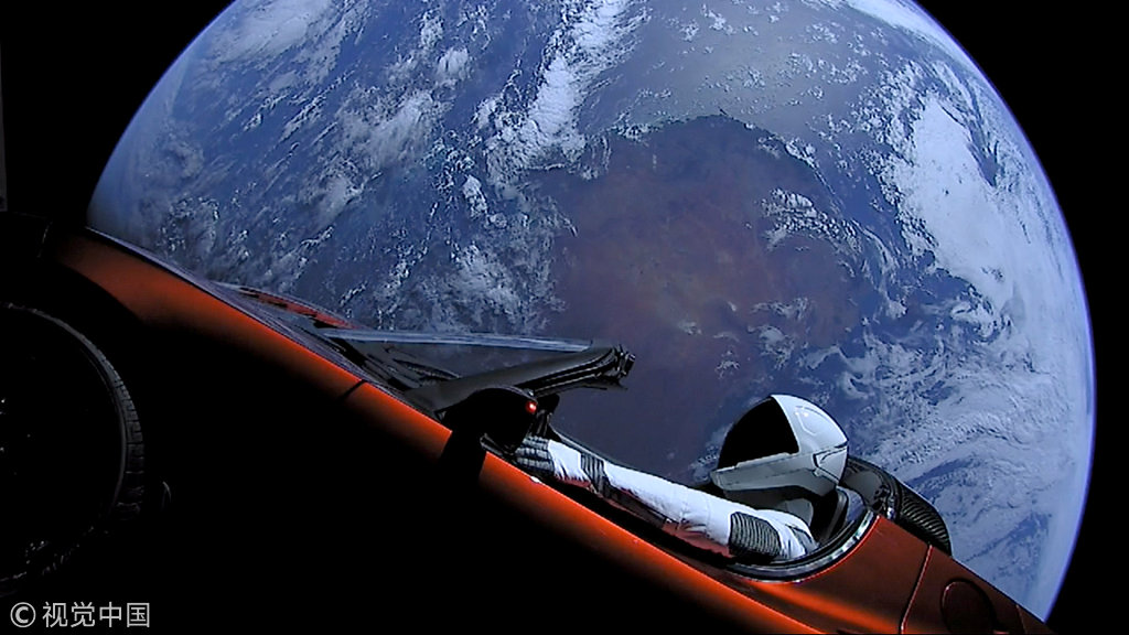 A cherry red Tesla Roadster automobile floats through space after it was carried there by SpaceX's Falcon Heavy in this image obtained by on February 9, 2018. [Photo: VCG]