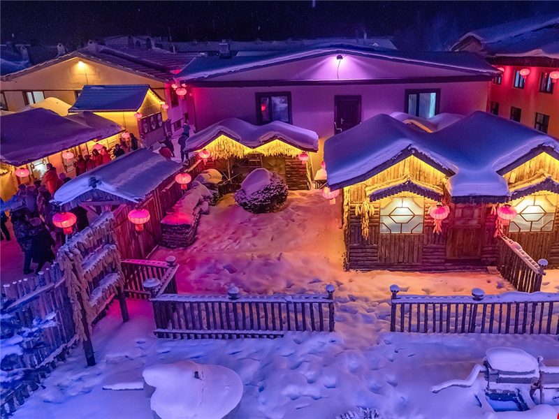 Tourists enchanted by the night scene in fairy tale snow town in NE China
