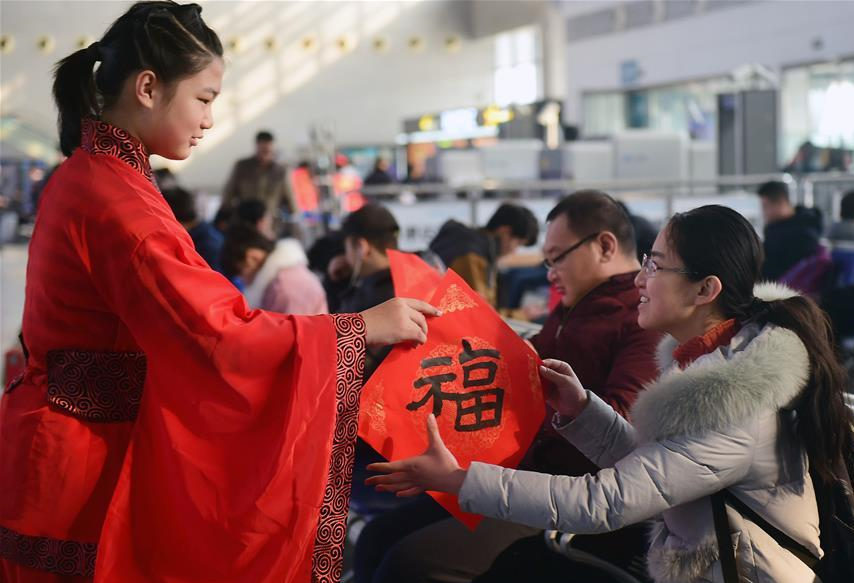 Pupils send calligraphy works to passengers at railway station in China's Hebei to greet Spring Festival