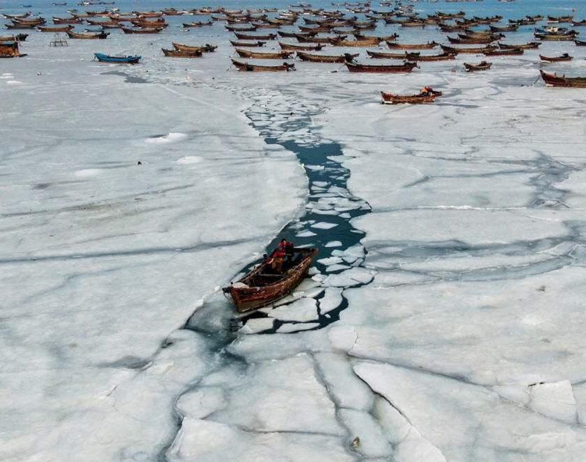 Fishermen break thick sea ice to continue work