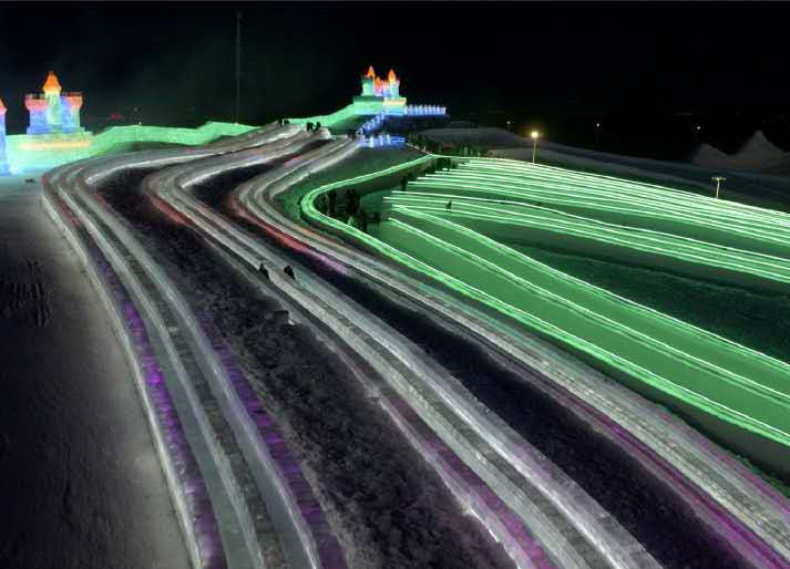 Visitors try the world's longest ice slide in North East China