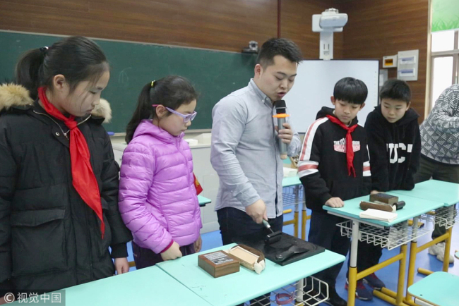 A craftsman specializing in Chinese characters demonstrates how to make a movable type printing at the West Lake Primary School in Hangzhou on Tuesday, March 5, 2019. [Photo: VCG]
