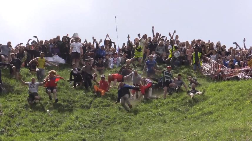 Competitors tumble down hill to take part in annual rolling cheese race